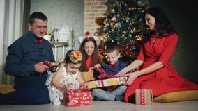 La familia grande alegre de cinco personas está abriendo los regalos de una Navidad Noche del Año Nuevo en el pie del árbol de na metrajes