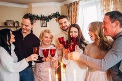 La familia grande celebra la Navidad y el champán de consumición imagenes de archivo