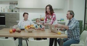 La familia grande por la mañana tiene una mamá madura hermosa del desayuno colorido sano que prepara la comida para sus muchachos metrajes