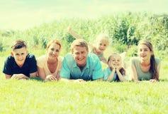 La familia grande que miente en la hierba en parque Fotografía de archivo libre de regalías