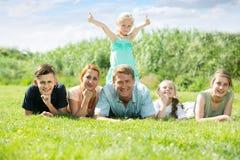 La familia grande que miente en la hierba en parque Foto de archivo libre de regalías
