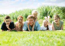 La familia grande que miente en la hierba en parque Fotos de archivo libres de regalías