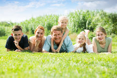 La familia grande que miente en la hierba en parque Imagen de archivo libre de regalías