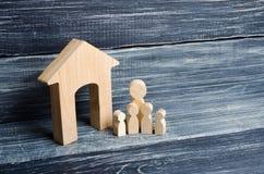 La familia grande se está colocando cerca de la casa Las figuras de madera de personas se colocan cerca de una casa de madera El  Imagenes de archivo