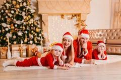 La familia hermosa en vestidos rojos miente debajo de un árbol de navidad imagenes de archivo