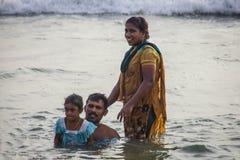 La familia hindú hace santo se baña en la confluencia sagrada en la playa de Papanasam Imagenes de archivo