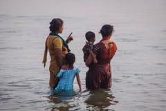 La familia hindú no identificada hace santo se baña en la confluencia sagrada en la playa de Papanasam Foto de archivo
