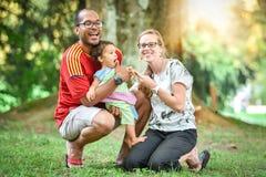 La familia interracial feliz está disfrutando de un día en el parque Imagenes de archivo