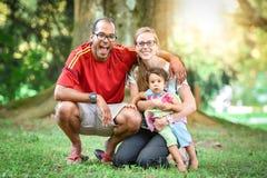 La familia interracial feliz está disfrutando de un día en el parque Imagen de archivo