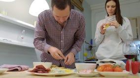 La familia joven cocina la pizza junta en la cocina almacen de metraje de vídeo