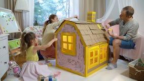 La familia joven con el edificio del niño y la pintura juegan la casa de la cartulina juntas metrajes