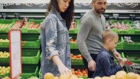 La familia joven con el niño alegre está caminando a través de tienda de alimentación con el carro de la compra y está eligiendo  metrajes