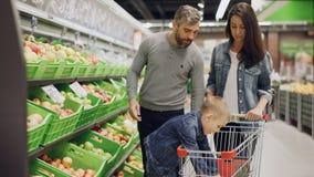 La familia joven con el niño está haciendo compras para la comida en supermercado, los padres están eligiendo la fruta y el mucha