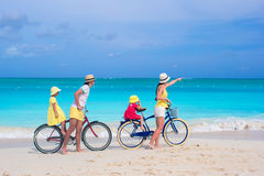 La familia joven con los niños monta las bicis en una playa exótica tropical Fotos de archivo
