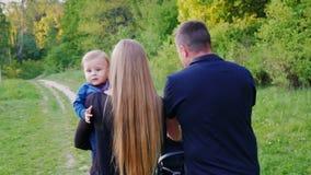 La familia joven con un niño está caminando en el parque, vista posterior Un bebé joven mira la cámara Forma de vida sana almacen de video
