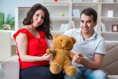 La familia joven de los pares que cuenta con a un bebé imagenes de archivo