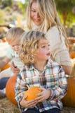 La familia joven disfruta de un día en el remiendo de la calabaza Imágenes de archivo libres de regalías