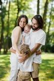 La familia joven elegante está teniendo resto en el parque El papá y la mamá están deteniendo a la hija en los brazos y están abr imagen de archivo libre de regalías