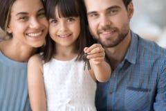 La familia joven emocionada con llaves del control del ni?o hace due?os de la casa imagenes de archivo
