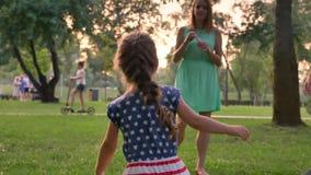 La familia joven está caminando en el parque en verano, hija está cogiendo las burbujas, concepto de la niñez metrajes