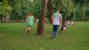 La familia joven está caminando en parque en el verano, padres está jugando la captura con la hija, jugando concepto metrajes