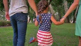 La familia joven está caminando en parque en la hija del verano, el sostenerse y el lanzar, jugando concepto metrajes