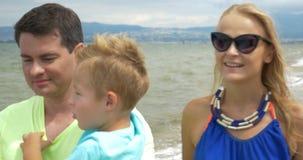 La familia joven está caminando a lo largo de la playa, teniendo una conversación y una sonrisa preciosas El papá lleva al bebé,  metrajes