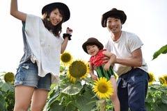 la familia joven está sonriendo con el campo del girasol Foto de archivo