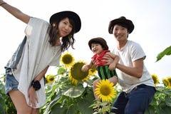 la familia joven está sonriendo con el campo del girasol Imagenes de archivo