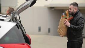 La familia joven est? embalando sus bolsos de ultramarinos al nuevo coche Hombre de Front View Of Handsome Bearded y mujer hermos almacen de metraje de vídeo