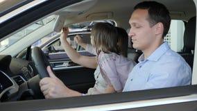 La familia joven examina el salón del coche, familia elige el auto, padres almacen de metraje de vídeo