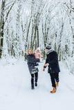 la familia joven feliz camina con el bebé en la calle del invierno, mamá, papá, c imágenes de archivo libres de regalías