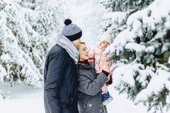 la familia joven feliz camina con el bebé en la calle del invierno, mamá, papá, c imagen de archivo libre de regalías