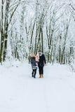 la familia joven feliz camina con el bebé en la calle del invierno, mamá, papá, c foto de archivo