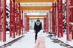 la familia joven feliz camina con el bebé en la calle del invierno, mamá, papá, c fotos de archivo libres de regalías