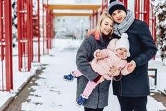 la familia joven feliz camina con el bebé en la calle del invierno, mamá, papá, c fotografía de archivo