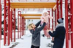 la familia joven feliz camina con el bebé en la calle del invierno, mamá, papá, c fotografía de archivo libre de regalías