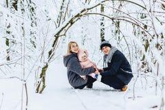 la familia joven feliz camina con el bebé en la calle del invierno, mamá, papá, c foto de archivo libre de regalías