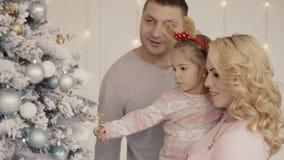 La familia joven feliz de la mamá, el papá, y la niña adornan un árbol de navidad almacen de metraje de vídeo