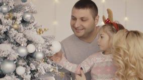 La familia joven feliz de la mamá, el papá, y la niña adornan un árbol de navidad almacen de video