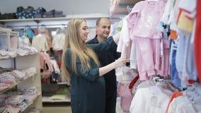 La familia joven feliz elige la ropa para su niño nonato Mujer embarazada en una tienda Tienda de las mercancías del ` s de los n metrajes