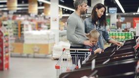 La familia joven feliz está haciendo compras en el supermercado, madre está comprobando la comida en envases, padre está hablando metrajes