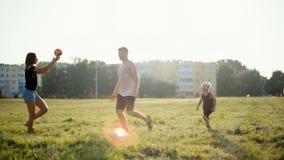 La familia joven feliz está jugando la bola con el niño en hierba en Niza la puesta del sol metrajes