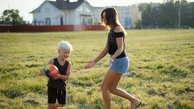 La familia joven feliz está jugando la bola con Little Boy en hierba en Niza la puesta del sol almacen de video