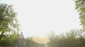 La familia joven feliz que tiene resto activo en el fin de semana, montando monta en bicicleta en el parque almacen de metraje de vídeo