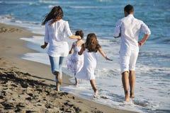 La familia joven feliz se divierte en la playa Imágenes de archivo libres de regalías