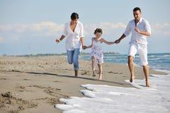 La familia joven feliz se divierte en la playa Fotografía de archivo libre de regalías