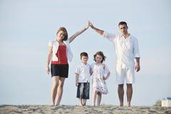La familia joven feliz se divierte en la playa en la puesta del sol Imagen de archivo