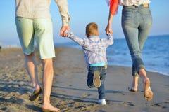 La familia joven feliz se divierte en la playa funcionada con y salta en la puesta del sol Imágenes de archivo libres de regalías