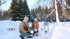 La familia joven lanza para arriba nieve en el aire almacen de video